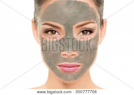 Clay mask facial treatment Asian beauty woman. Wellness and spa purifying peel off mask face portrait, isolated on white background. Cleansing skin care to remove blackheads and clean pores.