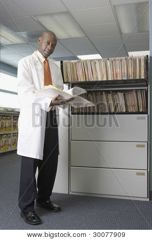 Portrait of male doctor reading files