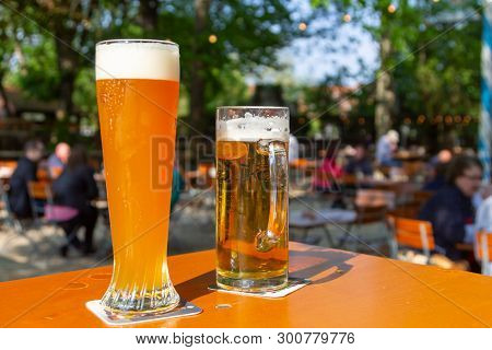 A Wheat Beer And A Pils Are Standing On A Table In A Beer Garden