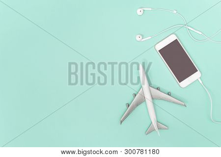 Mobile Phone And Toy Plane On Blue Teal Background For Travel Concept
