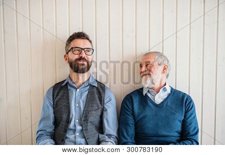 A Portrait Of Adult Hipster Son And Senior Father Sitting On Floor Indoors At Home.