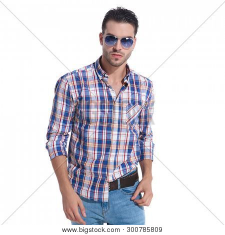 Serious looking guy staring straight to the camera while wearing sunglasses, a checkered shit and blue jeans, standing on shite studio background