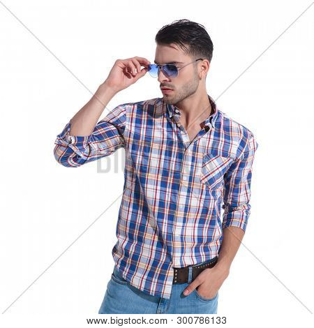 Mystified guy looking to the side and fixing his sunglasses while holding on of his hands in his pocket and wearing a checkered shite, standing on white studio background