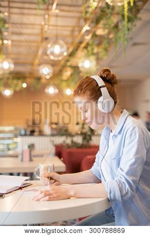 Pretty young woman in casualwear listening to music in headphones while preparing for seminar in college cafe