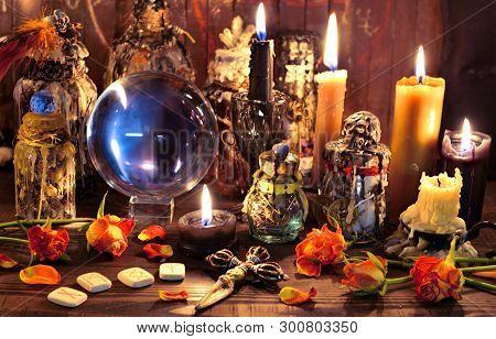 Crystal ball with runes, black candle and witch magic bottle. Wicca, esoteric, Halloween and occult background with vintage magic objects for mystic rituals poster