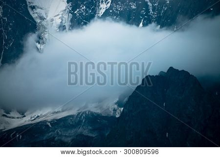 Low Cloud Before Huge Glacier. Giant Snowy Rocky Mountain Wall In Thick Fog. Early Morning In Mounta