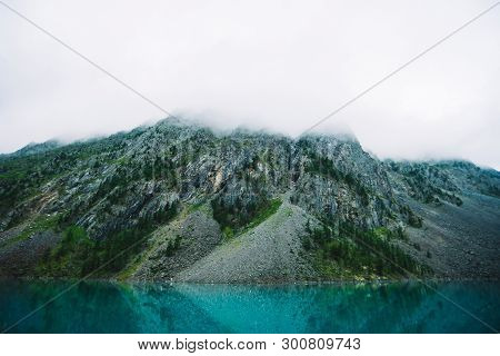 Giant Cloud Above Rocky Mountainside With Trees In Fog. Amazing Mountain Lake. Mountain Range Under