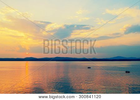 Sea landscape. Summer sunny water scene with unidentified people in the boat, concept of summer sea activities. Sea summer nature with mountain range at the horizon