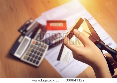 Women Use Scissors To Cut Credit Cards In Hand With Many Credit Card And Statement On Table For Back