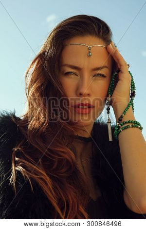 Portrait Of Fashionable Girl In Black Dress And Stilish Tiara With Green Jewellry In Her Hand In Sun
