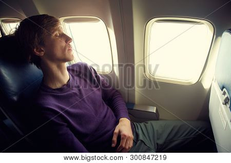Young Man Sleeping In An Airplane Seat. Traveler In An Plane.