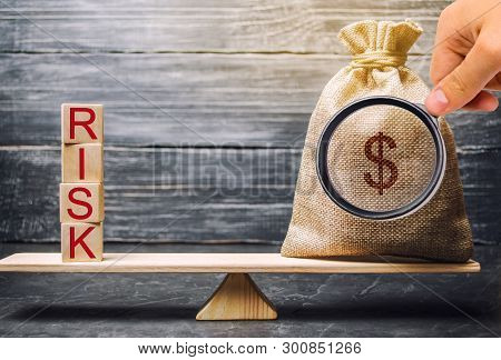 Money Bag And Wooden Blocks With The Word Risk. The Concept Of Financial Risk. Justified Risks. Inve