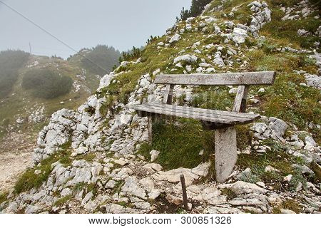 Old Vintage Bench In Mountain Stony Terrain In The Fog.