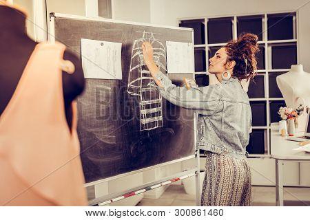 Designer Drawing A Sketch On A Blackboard.