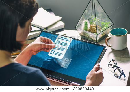 Woman With Laptop On Her Desk. She Holds A Questionnaire Icon. Concept Of Online Testing, Questionna