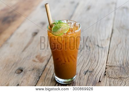 Ice Cold Sweet Lemon Tea Drink  On The Wooden Table With Outdoor Sun Lighting.