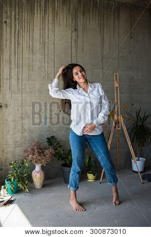 Beautiful Young Lady Artist In White Shirt Dancing Barefoot In Her Bohemian Artistic Studio Loft