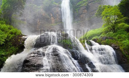 Big Waterfall Cascade With Water Splashing Creating Cataractagenitus Cloud On Background Then Stream