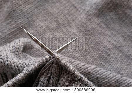 Incomplete knitting project with metal needles close-up. Knitting a gray wool sweater. The concept of hobby, creativity, needlework, handmade. poster