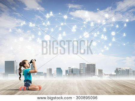 Cute Kid Girl Sitting On Wooden Floor And Looking In Binoculars