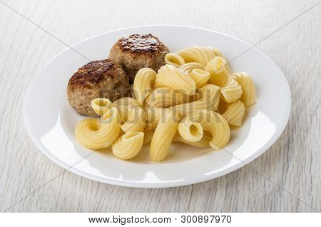 White Plate With Cooked Pasta Cavatappi, Fried Patties On Light Wooden Table