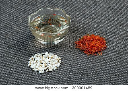 Saffron Flowers And Seeds In A Pile On The Table. Cosmetic Vegetable Oil In A Glass Cup. Safflower F