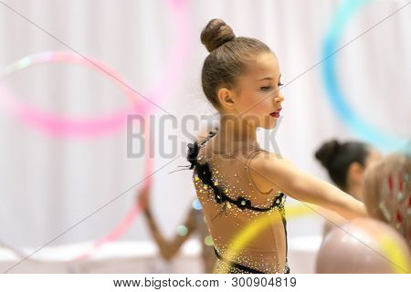 poster of Nice little gymnast girl performing a dance with a hoop, healthy active childhood, playing sports, taking part in a rhythmic gymnastics competition