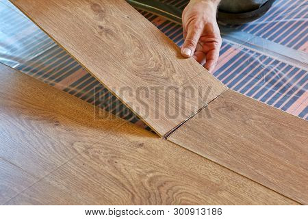 Laminate flooring. Male repairman is laying panel of  laminate floor  on a heat-insulated floor. Electrical floor heating system, radiant heating, infrared carbon heating film for floor