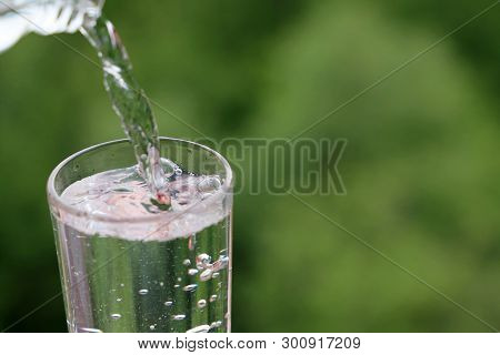 Clean Water Pours From A Bottle Into Drinking Glass On Green Nature Background. Concept Of Health An