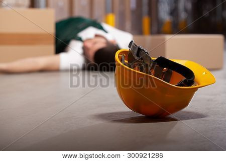 Yellow Helmet On The Floor After Dangerous Accident In Warehouse During Work