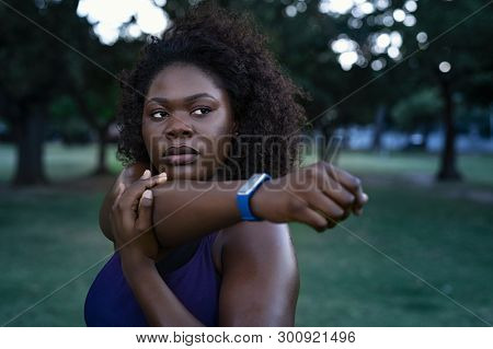African american woman with curly hair stretching at park. Black determined oversize girl working out during dusk. Portrait of focused overweight woman in sportswear doing stretching exercise.