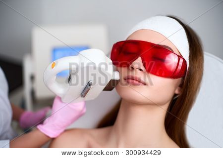 Beautician Doctor Doing Laser Rf Rejuvenation For Pretty Young Woman Face At Beauty Salon. Elos Epil