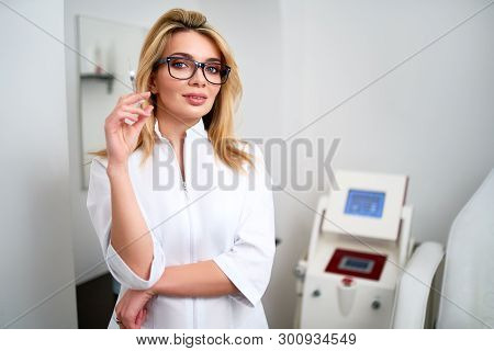 Portrait Of Young Attractive Beautician Doctor With Syringe In Hand. Cosmetologist Holding Medical T