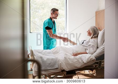 Surgeon Visiting And Shaking Hands With Mature Female Patient In Hospital Bed