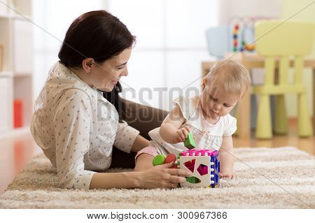 Woman And Baby Girl Playing With Developmental Toys In Nursery. Kid Learning Colors, Sizes And Shape