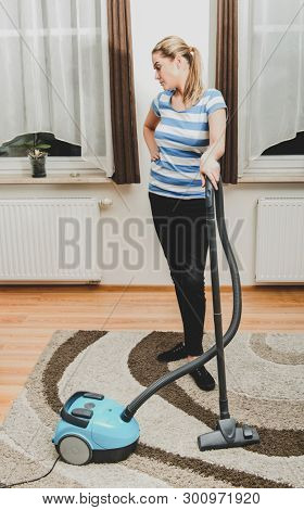 Young blond woman hoovering carpet at home. Housekeeping concept.