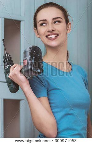 Smiling woman holding cordless in home interior. Craft and repair.