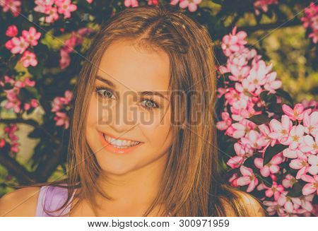 Portrait of young woman in the flowered garden for background.