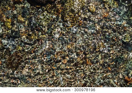 Varicolored Detailed Texture Of Stony Bottom Of Transparent Brook Close Up. Clean Water In Mountain