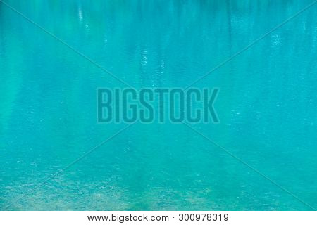 Shiny Texture Of Azure Surface Of Mountain Lake. Background With Reflection Of Green Mountains With