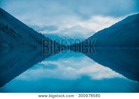 Amazing Silhouettes Of Mountains And Low Clouds Reflected On Mountain Lake. Beautiful Ripples On Wat
