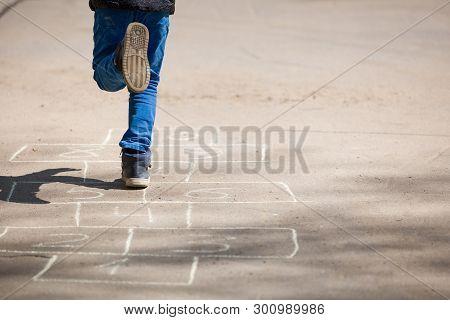 Child Boy Plays Hopscotch On Asphalt. A Child Plays Hopscotch On A Playground In A Park Outside On A