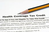 Close up of pencil on Health coverage tax credit poster