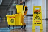 Mop bucket and caution sign inside a building poster