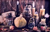 Witch bottles with pumpkin, black candles and paper scrolls. Wicca, esoteric, Halloween and occult background with vintage magic objects for mystic rituals poster