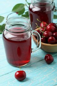Cherry Compote In A Glass Jar With A Handle On A Wooden Table Background