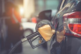 Car Gas Nozzle Refuel Fill Up With Petrol Gasoline At A Gas Station. Close Up. Gas Pump Nozzle In T