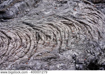 Smooth, Undulating Surface Of Black Frozen Lava. Frozen Lava Wrinkled In Tapestry-like Folds And Rol