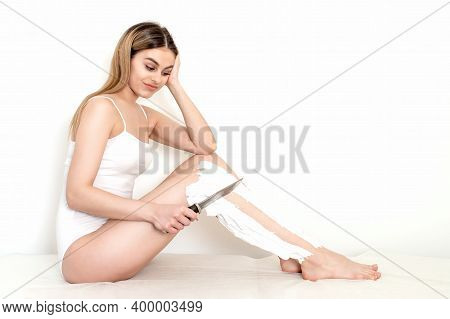 Beautiful Woman Shaving Her Legs With Knife Smeared With Shaving Foam On White Background. Depilatio