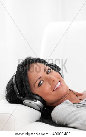 Beautiful latin girl listening music while lying on the sofa at home